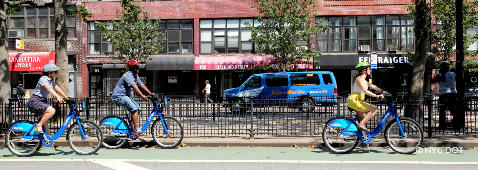 Three cyclists riding Citi Bike on Allen ST, in Manhattan