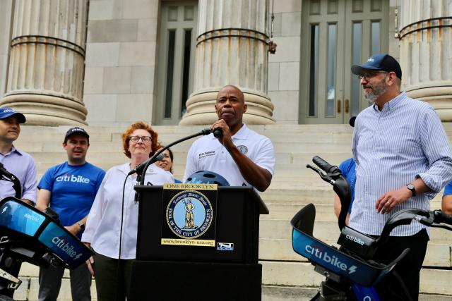 Brooklyn Borough President Adams in front of Brooklyn Borough Hall, surrounded by Pedal Assist Citi Bikes.