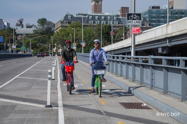 Two guys riding bikes, going towards the Staten Island Ferry Terminal. One man is in casual clothing and on a JUMP bike. The other man is in business-casual attire , riding a Lime Bike.