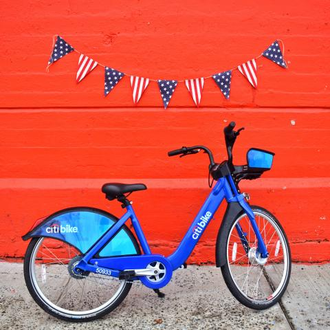 A Citi Bike under a stars & stripes banner.