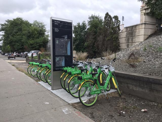 A row of Lime bikes neatly lined up near a Staten Island Railroad station.