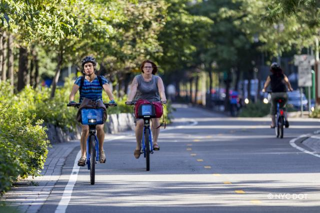 Two people riding CIti Bikes on the West Side Greenway.