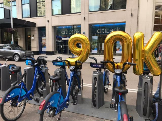 "Gold balloons reading ""90 K"" over a Citi Bike station."