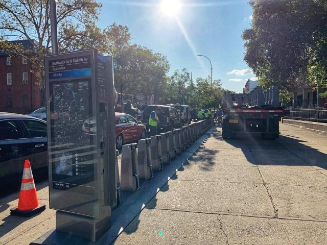 A crew working to install a Citi Bike station on a sidewalk.