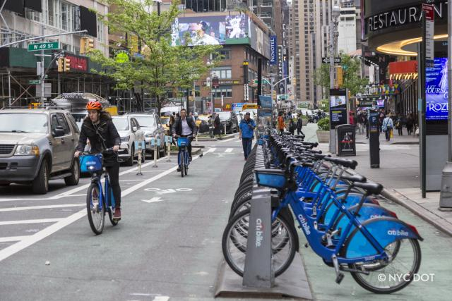 A Citi Bike station located next to a bike lane. There are two Citi Bike riders in the bike lane.