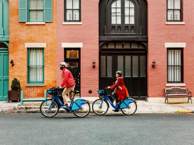 Two people riding Citi Bike e-bikes.