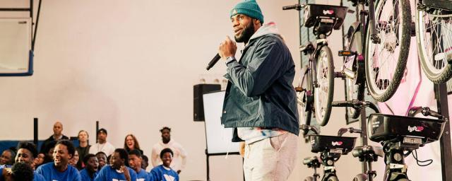 "LeBron James in front of crowd of teenagers at a YMCA in New York, with a row of ""Lyft"" bikes behind him."