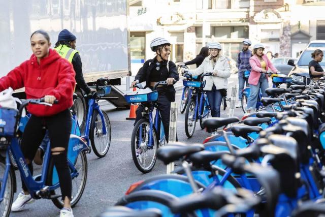 A photo of a group of people checking out multiple Citi Bikes.