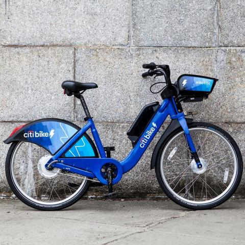 A photo of an electric Citi Bike against a wall.