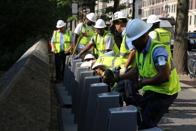 A photo of Citi Bike workers installing a station in the Upper East Side.