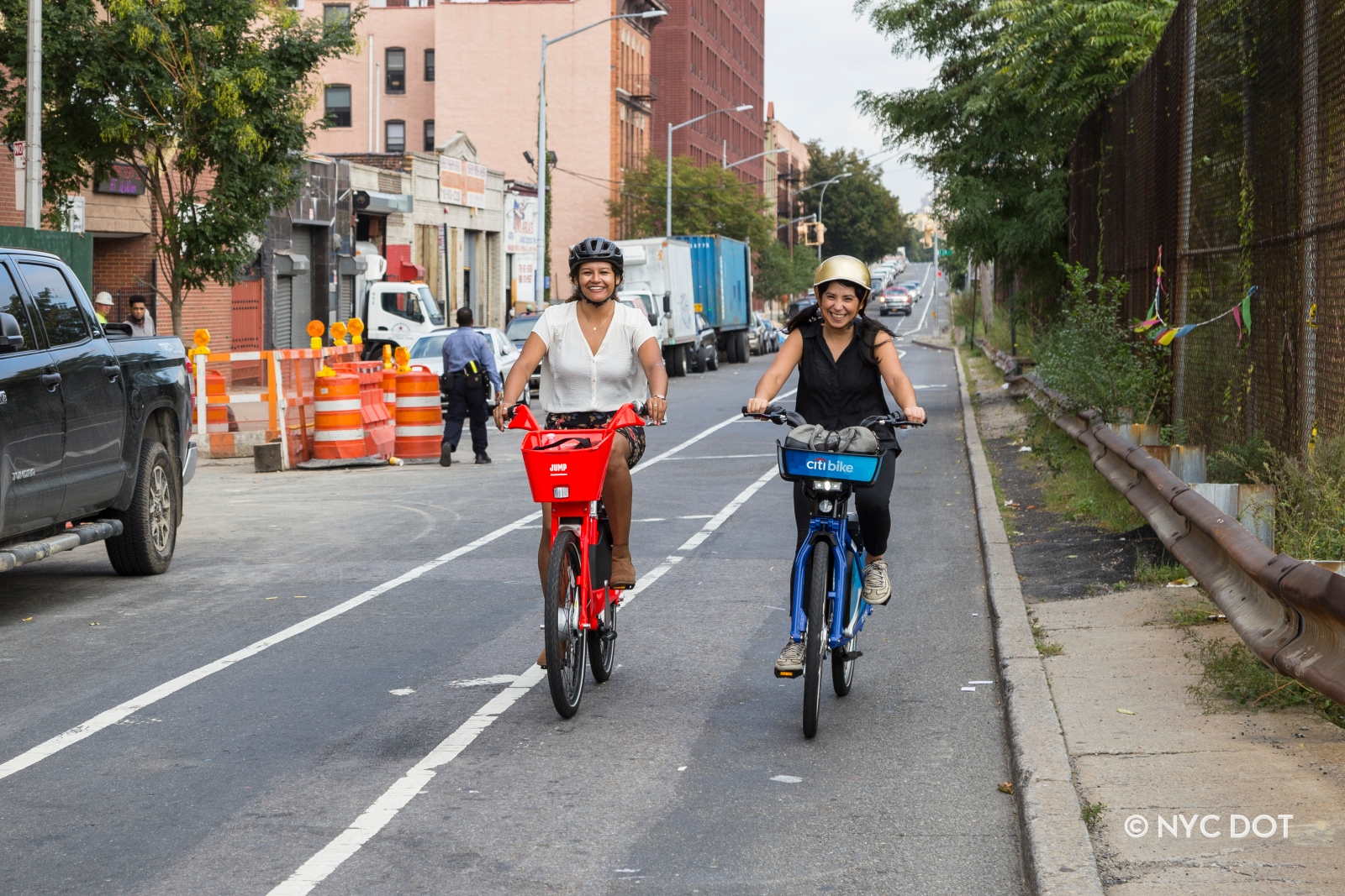 Two women riding dockless bike share in the Bronx. One is riding a red Jump bike, while the other is riding a blue Citi Bike.
